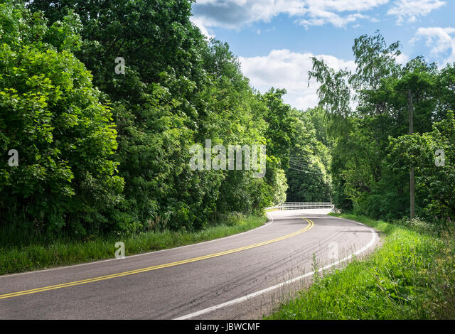 Landscape with curvy road at bright summer day - Stock Image