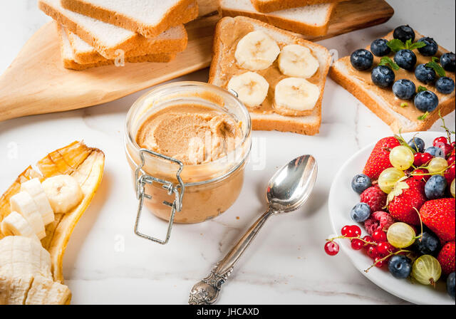 Traditional American and European summer breakfast: sandwiches of toast with peanut butter, berry, fruit apple, - Stock Image