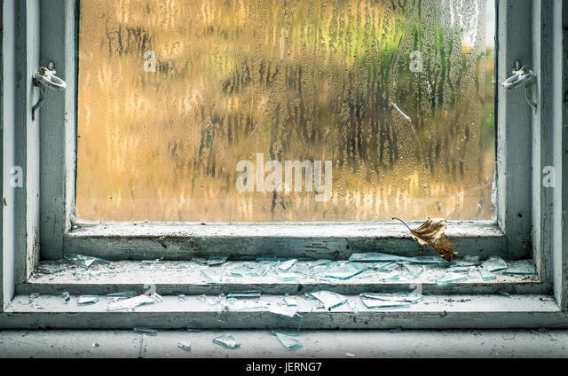 Broken window with fragment and emaciated leaf - Stock Image