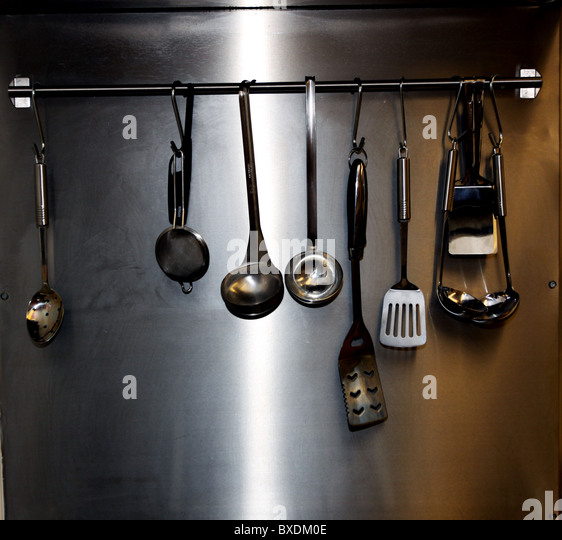 Cooking Utensils Hanging On Rail In Commercial Kitchen   Stock Image