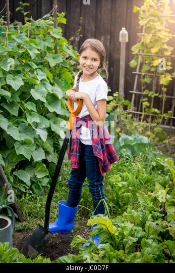 beautiful teenage girl posing at backyard garden with shovel stock image