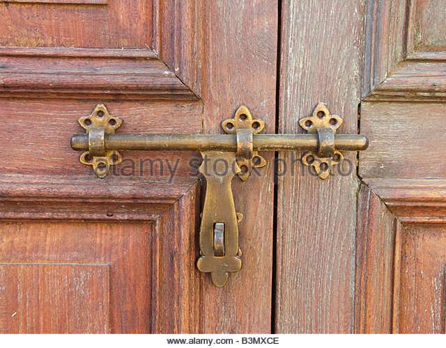 Old sliding door latch on vintage hardwood door - Stock Image - Old Door Brass Bolt Lock Stock Photos & Old Door Brass Bolt Lock