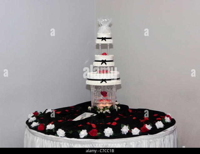 Multi Tier Wedding Cake With Water Fountain And Topper On A Table Decorated Black