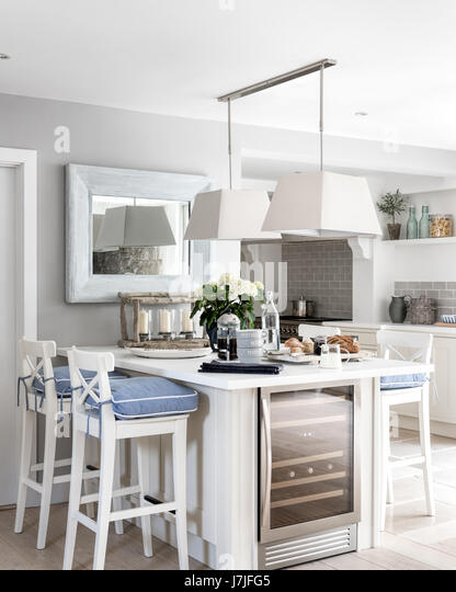 Breakfast bar with white Ingolf bar stools from Ikea and chambray seat pads from The White Company. The pendant - Stock Image