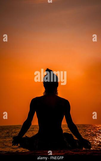 An Indian saint meditating on the beach while the sun sets. Sadhu Yogi ...