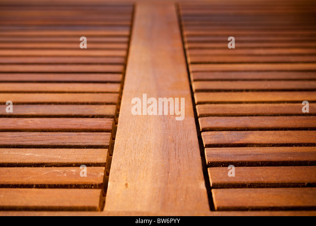 Thin timber slats form repeating patterns on a table top - Stock Image