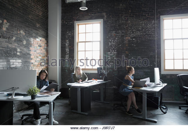 Creative business people working at desks in open plan loft office - Stock Image