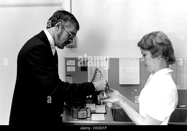 An Atomic Energy Commission Inspector Examines The Hands Of A Nuclear Medicine Technician For Possible Radioactive