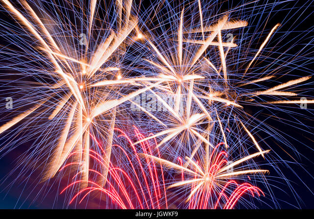 Details of fireworks, red, blue, orange, yellow and white with sky in the background - Stock Image
