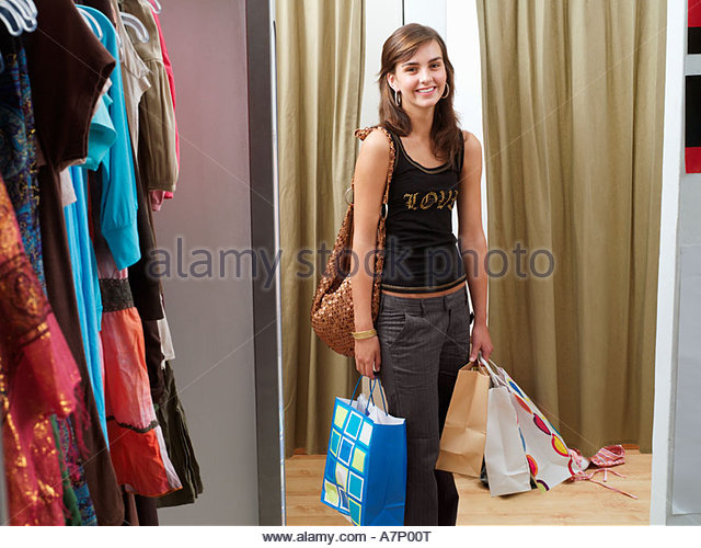Teenage girl 14 16 standing near fitting room in clothes shop carrying  shopping bags smiling portrait. Caucasian Teenage Girl In Dressing Stock Photos   Caucasian