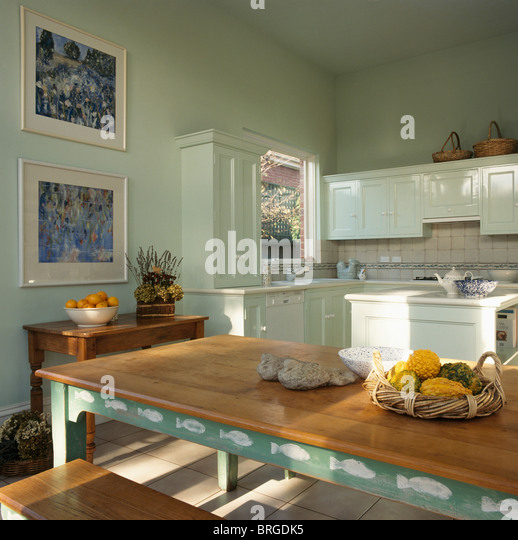 pastel green kitchen with green stenciled table with stripped wooden top stock image - Green Kitchen Table