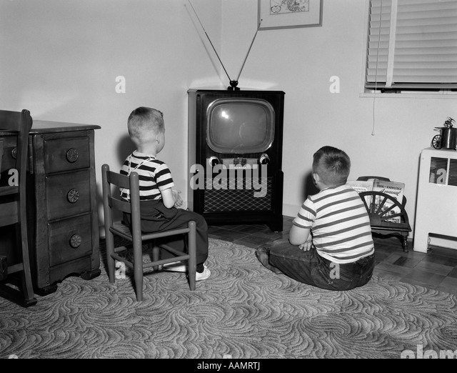black kids watching tv. 1950s two boys sitting in living room watching television - stock image black kids watching tv c