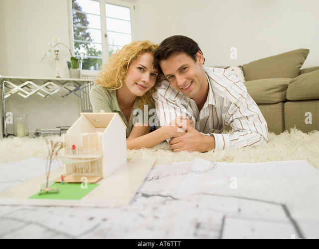 Couples looking at plans stock photos couples looking at for Living room ideas for young couples