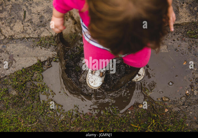 A 2-year old girl, looking down at ground and mud puddle, splashes in a mud puddle, making a mess of her clothes - Stock Image