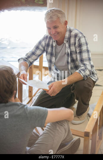Father And Son Building Furniture From Instructions   Stock Image