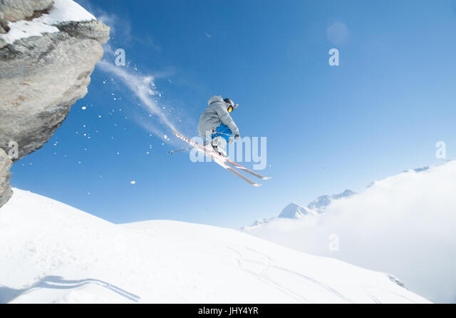 Skier going over a cliff trailing a spray of snow - Stock Image