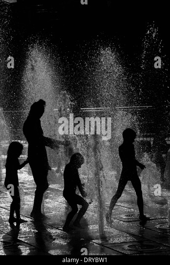 Silhouettes Of People Playing In Water Fountains