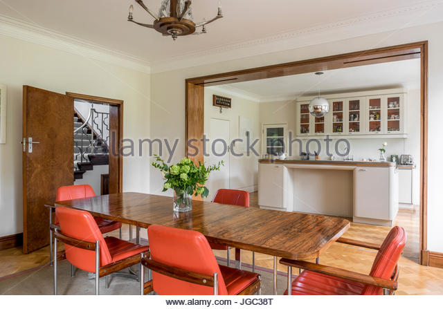Leather Dining Chairs At Polished Wooden Table With View Through Double Doors To Kitchen