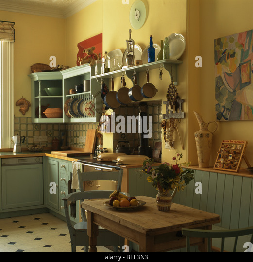 Old Pine Table And Chairs In Old Fashioned Yellow Kitchen With Green Fitted  Units