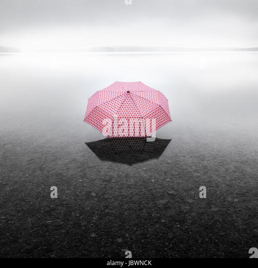 Pinky umbrella middle of the lake. This picture describes global warming. - Stock Image