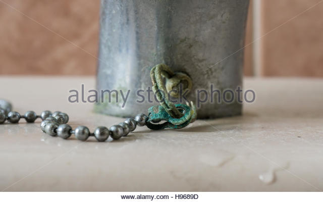 calcium deposits on chain bathroom sink stopper stock image