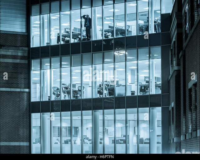 Man Looking Out Of Office Window At Night.   Stock Image