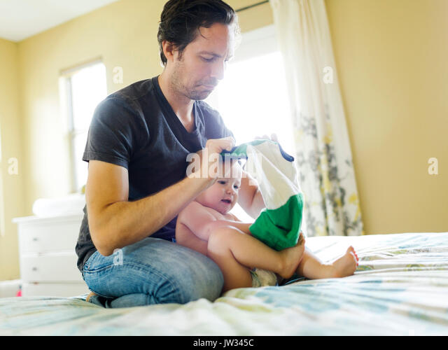 father dressing child stock photos father dressing child. Black Bedroom Furniture Sets. Home Design Ideas