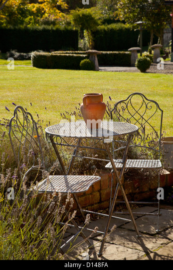 Metal French style garden furniture table and chairs with terracotta pot in  summer English garden. Typical English Garden Stock Photos   Typical English Garden Stock