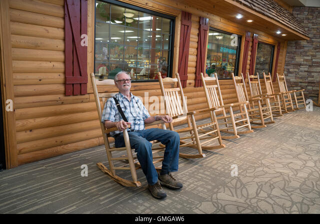 Man Relaxes In Rocking Chair Outside Shopping Mall Restaurant.   Stock Image