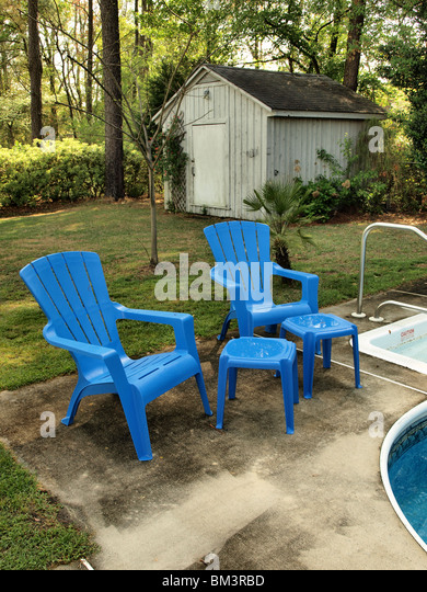 Backyard Garden Scene With Blue Lawn Pool Chairs At Edge Of Swimming Pool  With Shed And