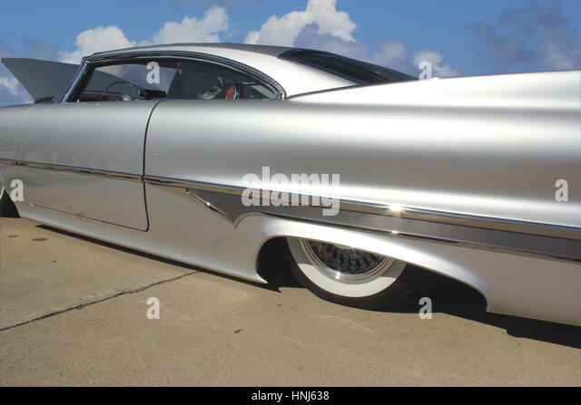 custom silver colored vintage car side view under blue sky stock image