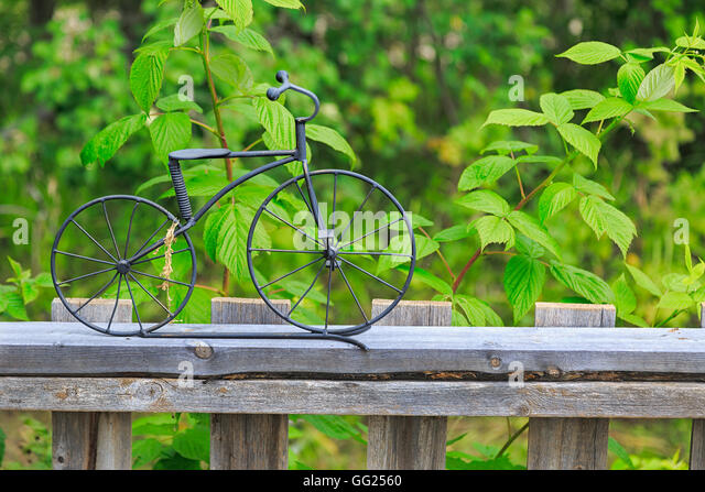 A Little Bicycle Ornament Made Out Of Wrought Iron On Top Of A Wooden Garden  Fence