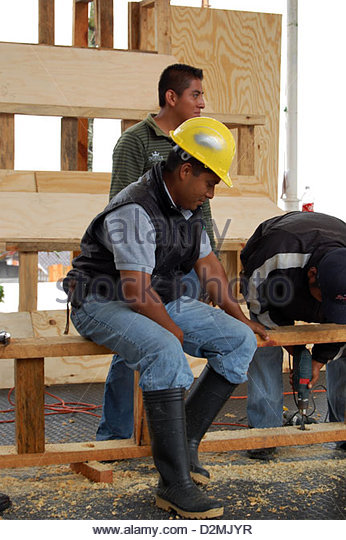 Mexican Male Construction Supervisor Watching Worker Drill Hole In Concert Stage Project With Hard Hat