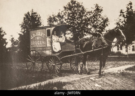 Two Women in a JB Hart Grocer delivery wagon in Minnesota USA 1907-1908 and having fun - Stock Image