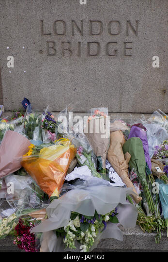Flower offerings on the pavement by London Bridge, where people were killed and wounded in a terrorist attack on - Stock Image