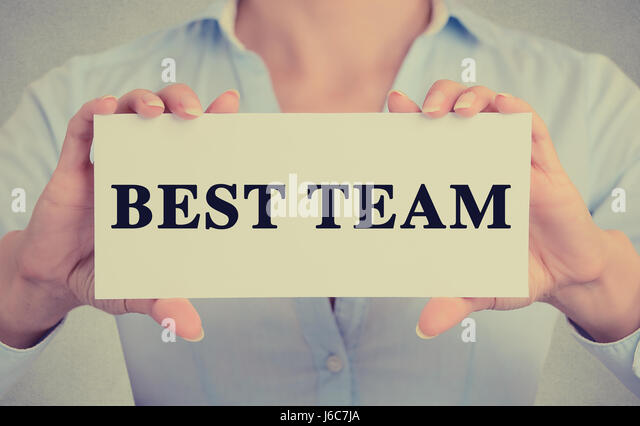 Closeup businesswoman hands holding white card sign with best team text message isolated on grey wall office background. - Stock Image