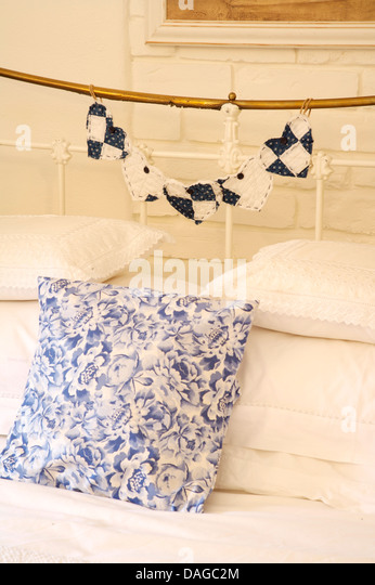 closeup of blue floral cushion on antique brass bed with cotton heart decoration and - Brass Beds