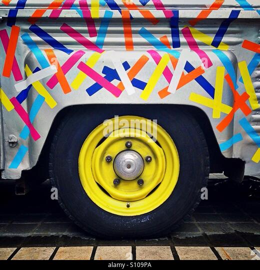 close up of brightly painted van in artistic abstract colours with yellow hub cap stock