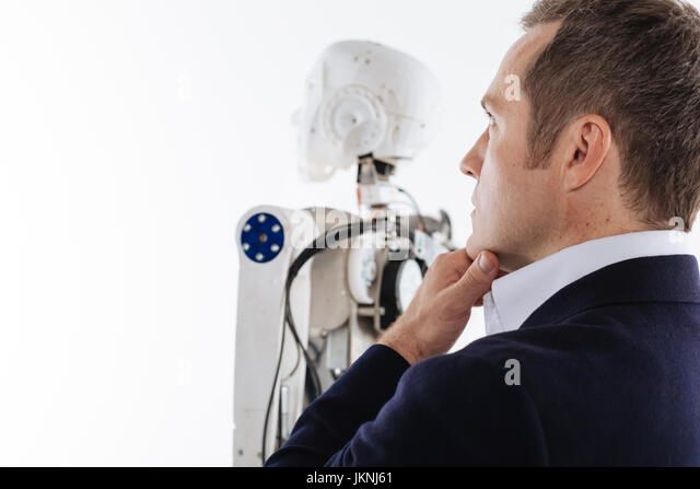 Thoughtful young inventor looking up and forward - Stock Image