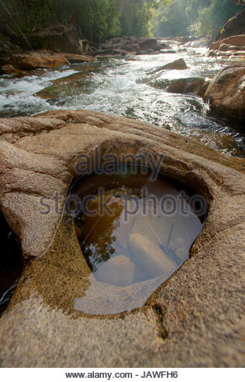 Granite rock lined riverbed with potholes in the upper Siduk River deep in Gunung Palung National Park's pristine - Stock Image