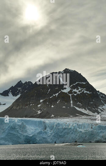 The blue-white front of a glacier reaches the sea over a boulder beach in Spitzbergen with a dim sun showing through - Stock Image