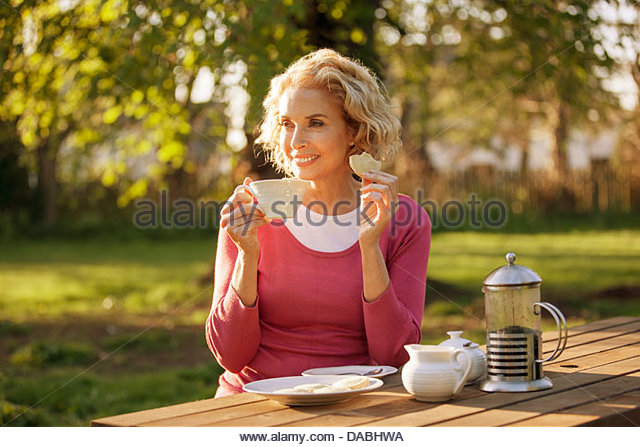 a mature woman having coffee and biscuits in a garden dabhwa Ginger And White Coffee Three Biscuits Stock Photo Image