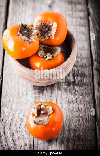 Persimmons on a wooden table - Stock Image