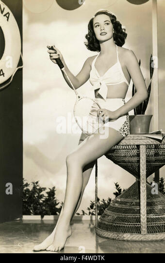 Actress dorothy malone in a white swimsuit with a squash racquet