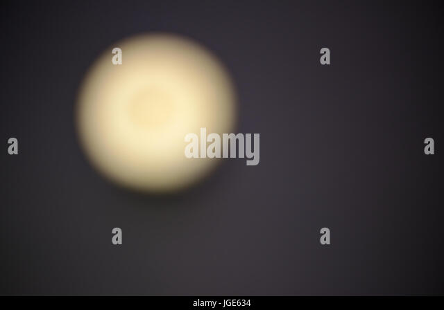 Abstract Lemon Stock Photography. Unfocused blurred lemon with a dark background. - Stock Image