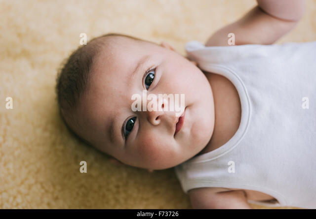 A Baby Girl Lying On Her Back On A Sheepskin Rug.   Stock Image