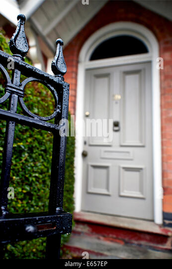 house front door open. An Open Front Gate Leading To A Hedge And Grey Door Of Terraced Victorian House