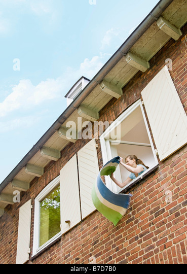 Woman Cleaning A Rug Out A Window   Stock Image