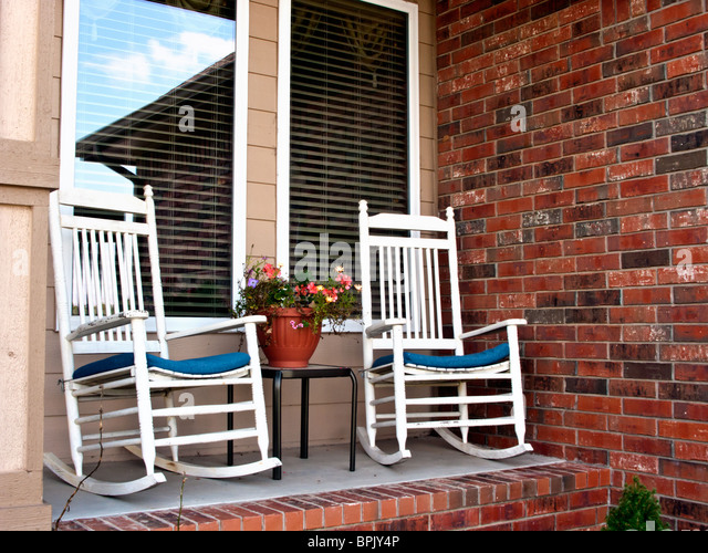 Two Rocking Chairs Sit On The Small Porch Of A Modern Brick Home Stock