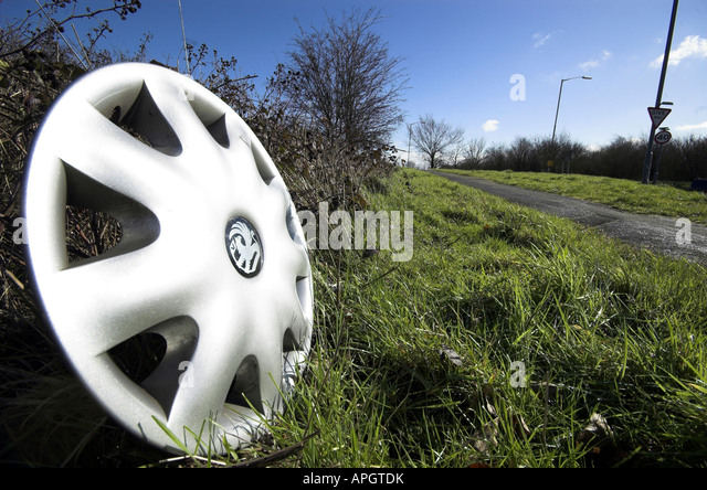 silver wheel hub cap discarded at the side of the road on a sunny day